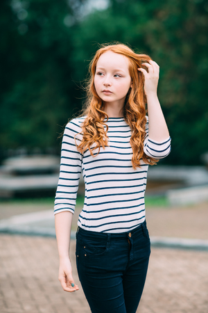 Outdoor portrait of beautiful girl with long curly red hair and green eyes. Young redhead woman touching her ginger hair. Teenage red-haired girl standing  in summer park. Femininity concept