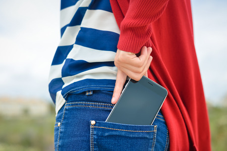 Foto de Closeup on woman hand takes out smartphone of her rear pocket of jeans on outdoors background - Imagen libre de derechos