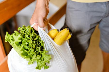 Foto de Male carrying bag in his hand after shopping. Closeup of bag full of fruits and vegetables. - Imagen libre de derechos