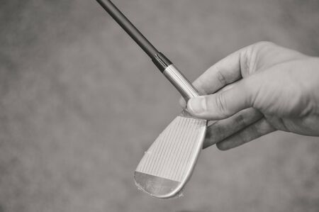Black and white picture of golf club in hand, copyspace background