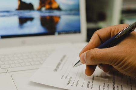 Photo for Closeup of hand writing filling job or service application form over light desk background. Signing with pen checklist, college student or education university program certificate. Business contract - Royalty Free Image
