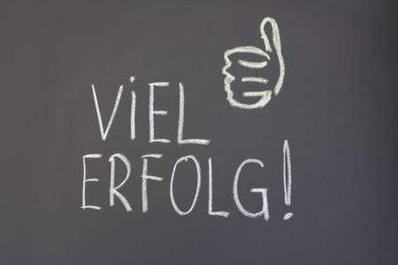 inscription in chalk on a blackboard, viel erfolg!