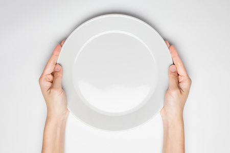 Photo pour Female(woman) two hands hold(support) a white dish(plate) isolated white and top view. - image libre de droit