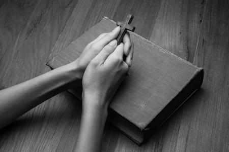 Photo pour Hands folded in prayer over Holy Bible - image libre de droit