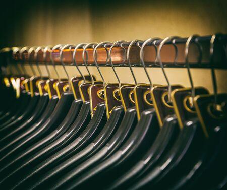 Foto de lot of plastic black hangers on the bar. Concept store, sale, design, empty hangers. - Imagen libre de derechos