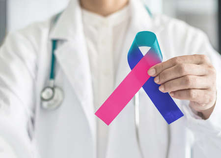 Photo pour Thyroid cancer awareness ribbon in Teal Pink Blue symbolic bow color in doctor's hand to support patient with tumor illness - image libre de droit