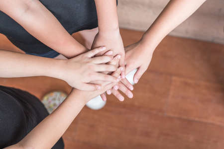 School kid volunteer hands for friendship, student's teamwork togetherness, children's day and community collaboration concept