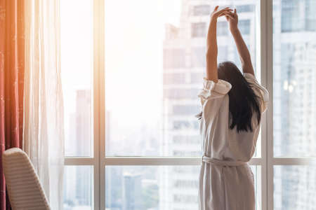 Photo pour Happy life quality balance concept with young girl take it easy lifestyle waking up in weekend morning having some rest relaxing in comfort city hotel room enjoying world lazy day - image libre de droit
