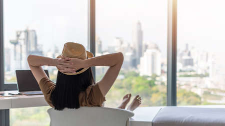 Photo pour Work and travel lifestyle relaxation and healthy work-life balance with young freelancer Asian working woman take it easy happily resting in comfort luxurious hotel guest room with peace of mind - image libre de droit