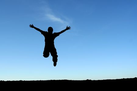 A happy man jumping in the air, in silhouette
