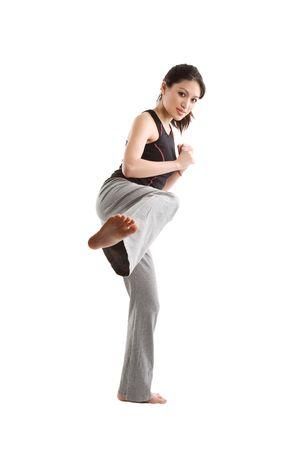 An isolated shot of happy beautiful asian woman doing a martial arts kicking