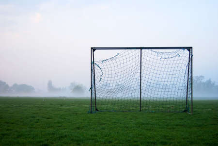 Soccer goal on a sports field on a foggy mornig