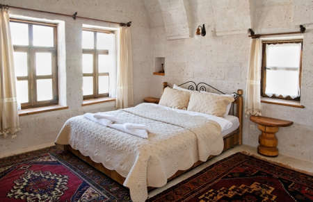 interior detailing of bedroom under the limestone arches, white detailed bedspread and cushions furniture, woven mats and net curtains. Landscape, copy space and crop area