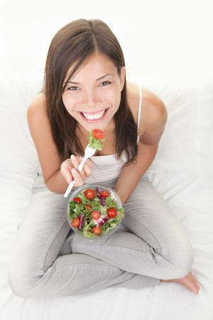 Woman eating salad. Beautiful healthy smiling mixed Asian Caucasian woman enjoying a fresh healthy salad sitting in bed looking up. High angle view with copy space on white background.