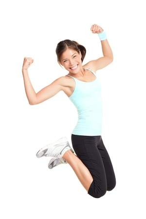 Fitness woman jumping excited isolated on white background. Full body image of beautiful multiracial Asian Caucasian female model in jump flexing and showing muscles.
