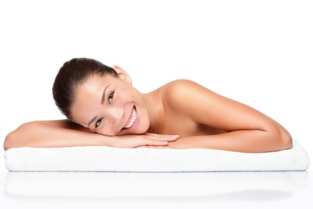 Spa. Face skincare beauty woman smiling happy. Portrait of beautiful attractive mixed race Chinese Asian / Caucasian female model lying down on towel during skin care treatment. Girl isolated on white background.