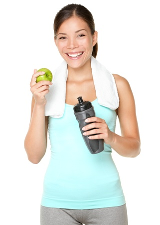 Foto de Healthy lifestyle - fitness woman eating apple smiling happy looking at camera. Pretty mixed race Caucasian Asian woman isolated on white background. - Imagen libre de derechos