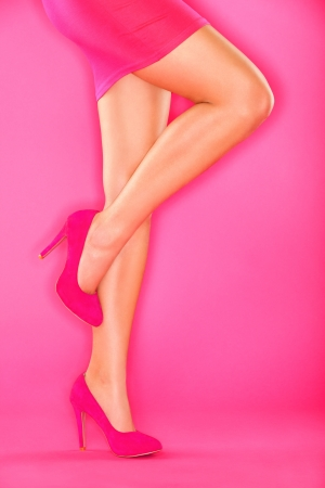 Pink high heels shoes and sexy woman legs in pink skirt on pink background. Beautiful female legs and shoes.
