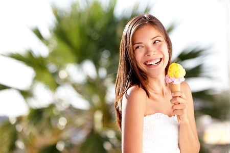 Ice cream woman looking at copy space happy, joyful and cheerful  Cute multiracial Caucasian   Chinese Asian young female model eating ice cream cone on summer beach