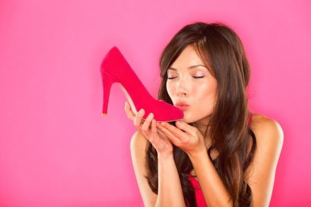 Woman kissing shoe  Women loves shoes concept  Multiracial girl and pink high heels shoes on pink background  Beautiful young happy mixed race Asian Chinese and Caucasian female model