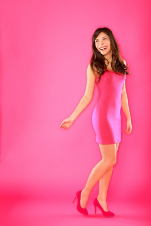 Woman portrait in full body length of young Asian Brunette standing playful in pink dress smiling looking over shoulder at copyspace on pink background.