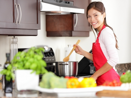 Cooking woman in kitchen stirring in pot making food for dinner  Young housewife smiling happy looking at camera  Mixed-race Caucasian   Asian chinese woman in her twenties