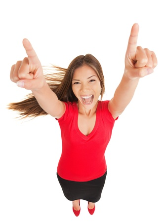 Successful woman cheering in jubilation laughing and pointing her hands to the sky