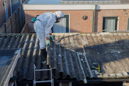 Foto de Professional asbestos removal. Men in protective suits are removing asbestos cement corrugated roofing - Imagen libre de derechos