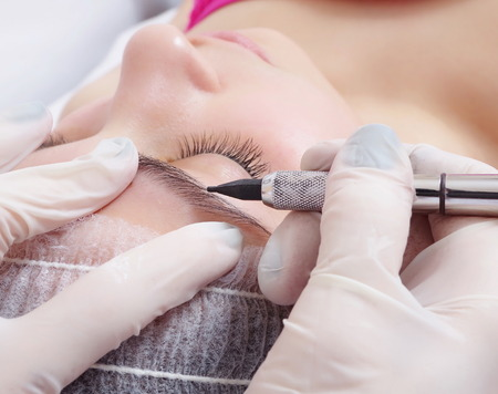 Foto de tattooist is using  gun tool for eyebrows tattoo closeup - Imagen libre de derechos
