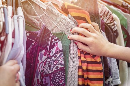 Foto de close up of a hand, looking on a flea market for clothes. - Imagen libre de derechos