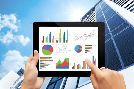 Foto de hand holding digital tablet  with analyzing graph against office buildings with sun - Imagen libre de derechos