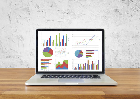 Photo pour Laptop on wooden table showing charts and graph with white cement wall ,Analysis Business Accounting, Statistics Concept. - image libre de droit