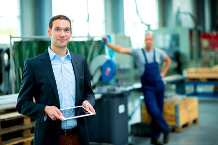 Photo pour young boss with worker in the background in his factory - image libre de droit