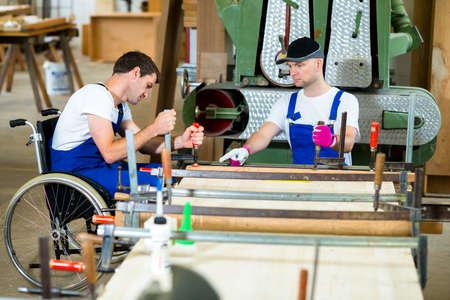 Foto de disabled worker in wheelchair in a carpenter's workshop with his colleague - Imagen libre de derechos