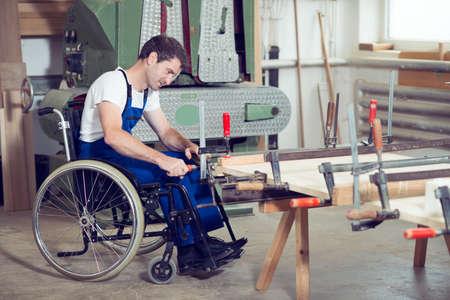 Foto de disabled worker in wheelchair in a carpenter's workshop - Imagen libre de derechos