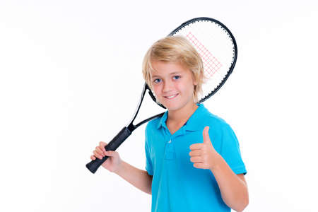 blond boy with tennis racket and thumb up in front of white background