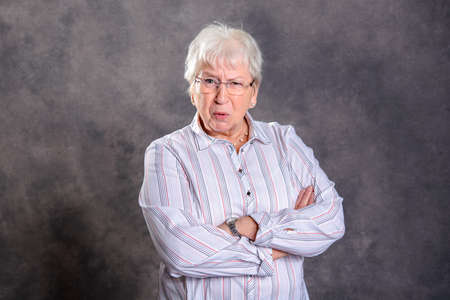 Foto de gray hairy elderly woman with crossed arms looking angry in front of gray background - Imagen libre de derechos