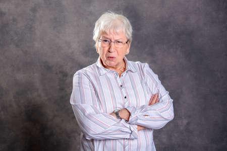 Foto de gray hairy elderly woman with crossed arms looking angry in front of gray background - Imagen libre de derechos