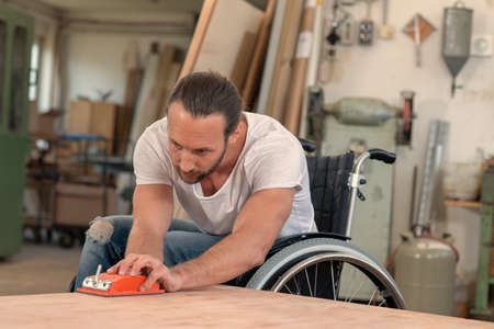 Photo for disabled worker in wheelchair in a carpenter's workshop - Royalty Free Image