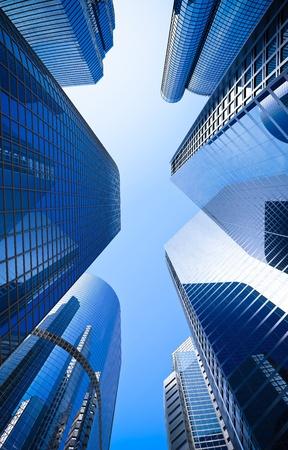 Foto de street of highrise glass skyscraper buildings low angle shot in blue dominant against a clear sky - Imagen libre de derechos