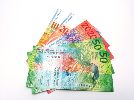 Foto de Swiss franc bank notes arrange like paper fan on  white background with cliiping path - Imagen libre de derechos