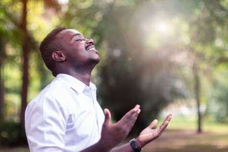 Foto de African man praying for thank god with light flare in the green nature - Imagen libre de derechos