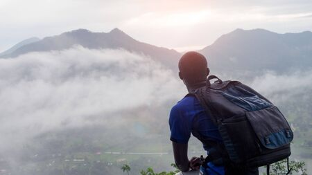 Photo for African man hiker with backpack at the top of the hill covered with mist.16:9 style - Royalty Free Image