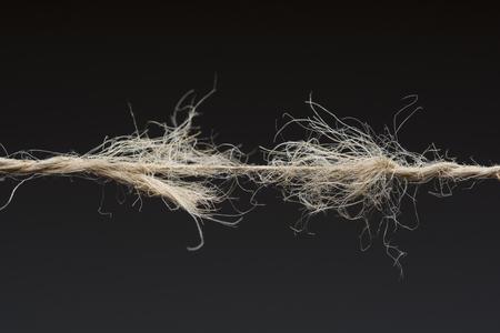 Foto de Frayed rope ready to break on dark background - Imagen libre de derechos