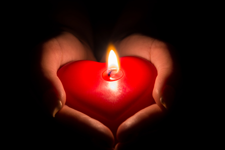 Photo pour woman's hands holding a heart shaped candle in the dark - image libre de droit