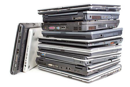 Pile uf used laptops, white background