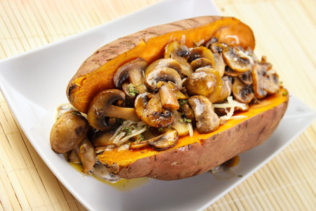 Photo for Oven cooked sweet potato , filled with mushroom sauce and roasted champignons - Royalty Free Image
