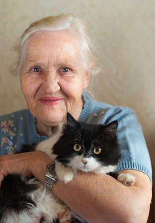 Photo pour Smiling happy elderly woman with her cat. Selective focus on a cat - image libre de droit