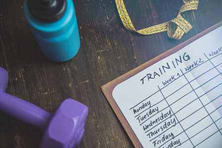 Photo pour High Angle View Of A Workout Plan In Notebook At Wooden Desk - image libre de droit