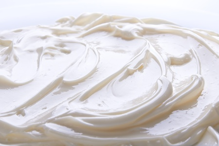 Wavy surface of light beige low-fat milky cream. Close-up photo.